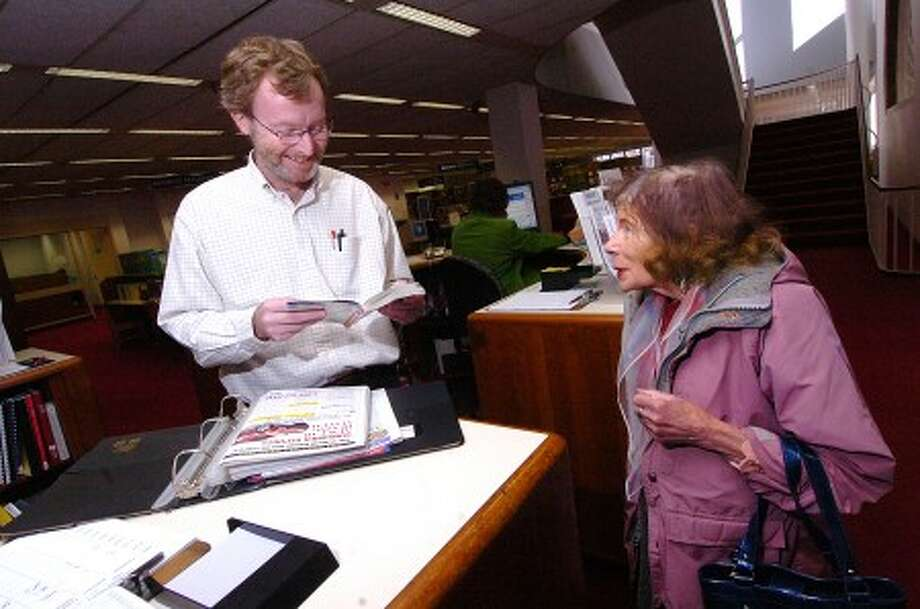 Photo/Alex von Kleydorff. Ferguson Library Information Services Supervisor Bill Miller helps a customer find some information in a Consumer Reports publication.