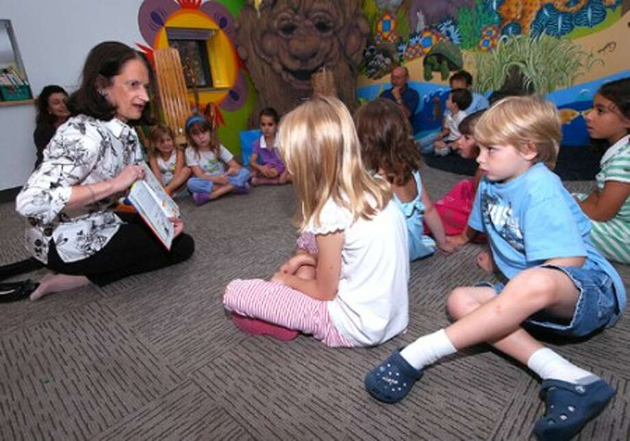 Photo/Alex von Kleydorff. Martine Berliet reads in french, '' Je Veux ma Banane'' to kids in the story room during French Story time at the Wilton Library.