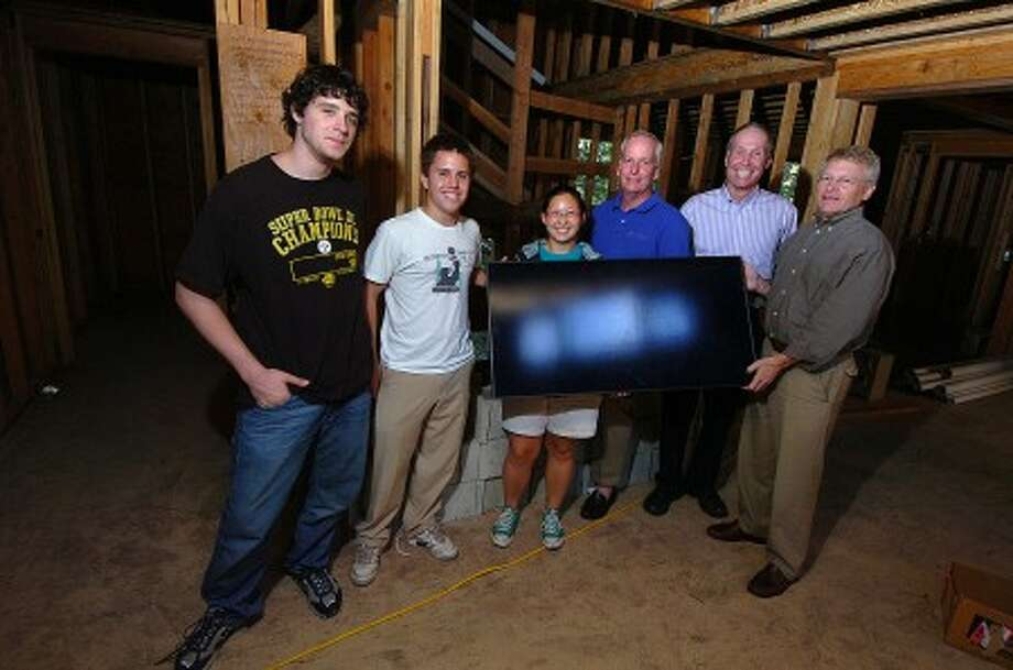 Photo/Alex von Kleydorff. Energy efficient vollunteer builders L-R, Daniel Chalons-Browne, Reed Dempsey, Alison Pogust, Tim Seamans, Jim Lyle and Ron French. Present a solar panel, part of the energy saving devices built into a Bridgeport home.
