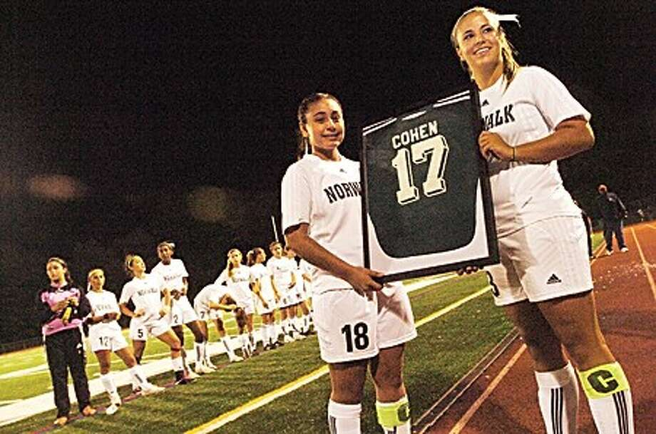 Norwalk girls soccer players, Anamilena Moreno and Sara Costa hold up the retired jersey of the late Chelsea Cohen who was a Norwalk high school student and played for the school''s soccer team/hour photo matthew vinci
