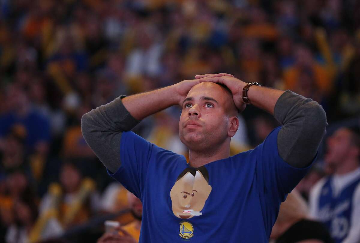 A fan reacts during the end of Game 6 of the NBA Finals between the Warriors and the Cavaliers during the Warriors Official Watch Party June 16, 2016 in the Oracle Arena Oakland, Calif.