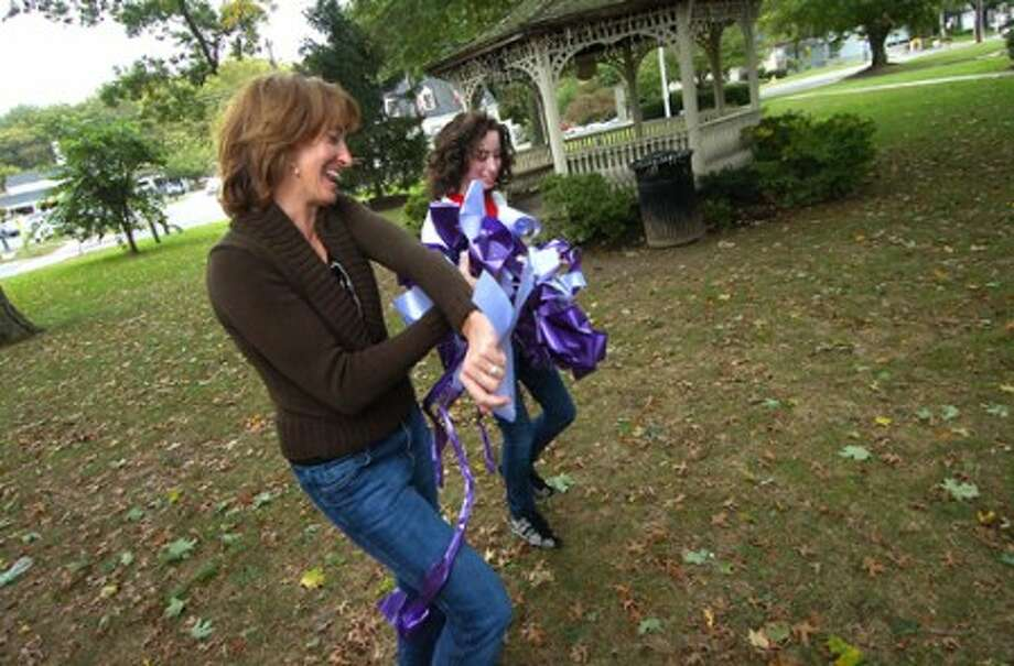Photo/Alex von Kleydorff. Janienne Hackett and daughter Sarah works with the purple ribbons for Domestic Violence Awareness Month on the Town green in Wilton center