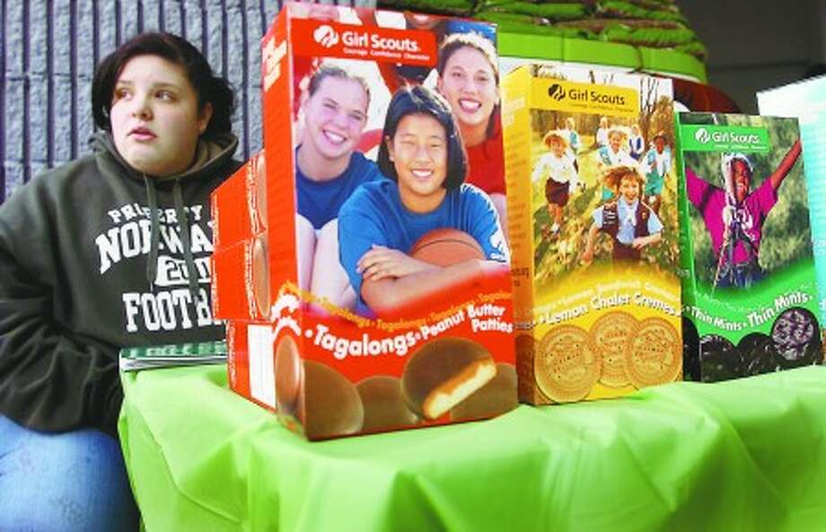Caroline Ross, age 15, of Girl Scout Troop 627, waits for customers to buy the famous Girl Scout cookies outside Walmart on Main Ave Friday. Sales are down significantly in the depresssed economy. Hour photo / Erik Trautmann