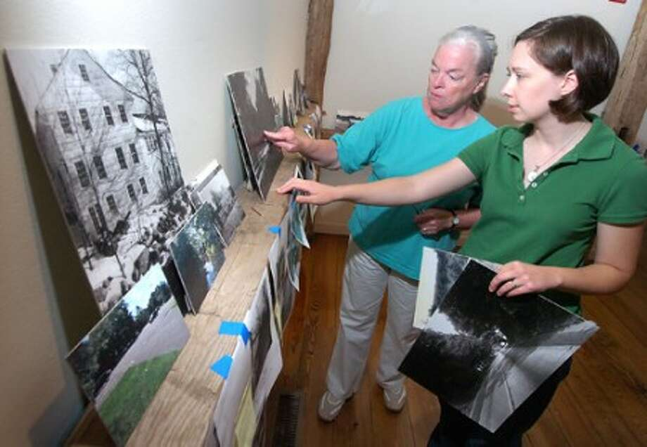 Photo/Alex von Kleydorff. l-r Wilton Historical Society Archivist Scotty Taylor and Curator Andrea Wulffleff prepare the Route 7 exhibit in one of the galleries.