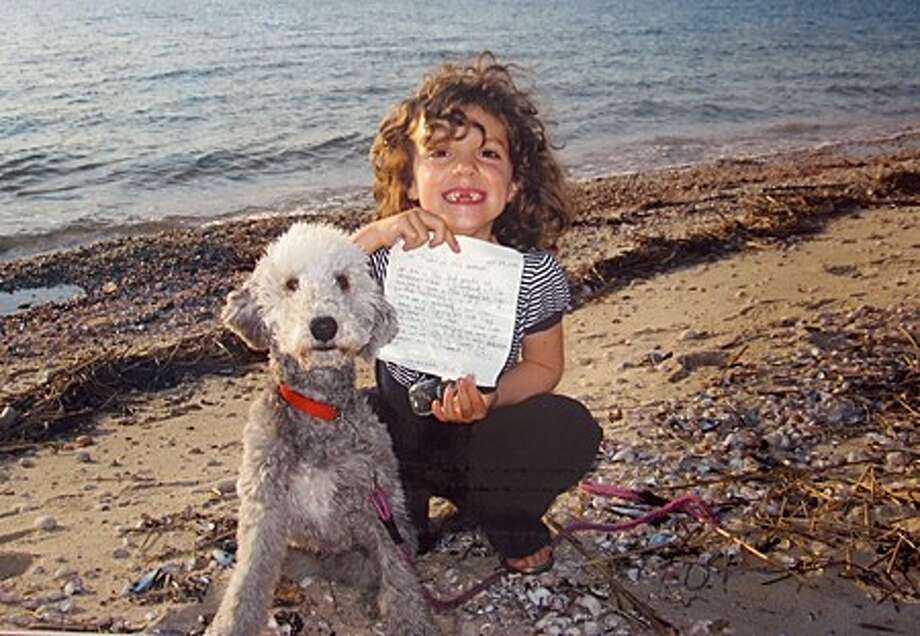 Olivia Hosie, a kindergarten student from Trinity Catholic School in Long Island found one of the messages in a glass bottle which Mrs. Wuest''s class at Westover Elementary School in Stamford tossed into Long Island Sound two months ago. The class received correspondences from one other student in Long Island who found a bottle on the shore. contributed photo