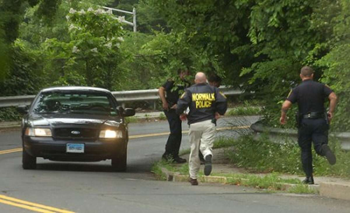 Photo/Alex von Kleydorff. Norwalk police respond to a wooded area off the Stuart Ave. overpass along northbound 195, in search of a man wanted in connection with a double homicide on Couch St.