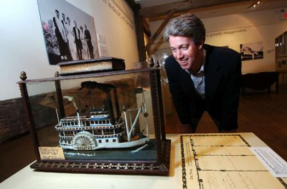 Photo/Alex von Kleydorff. Tierney O''Hearn, Co President of the Board of Directors at The Wilton Historical Society, looks over a hand carved Steamboat, crafted in prison by one of the burglars that had broken into his home, and was then sent to Twain after corresponding with him.