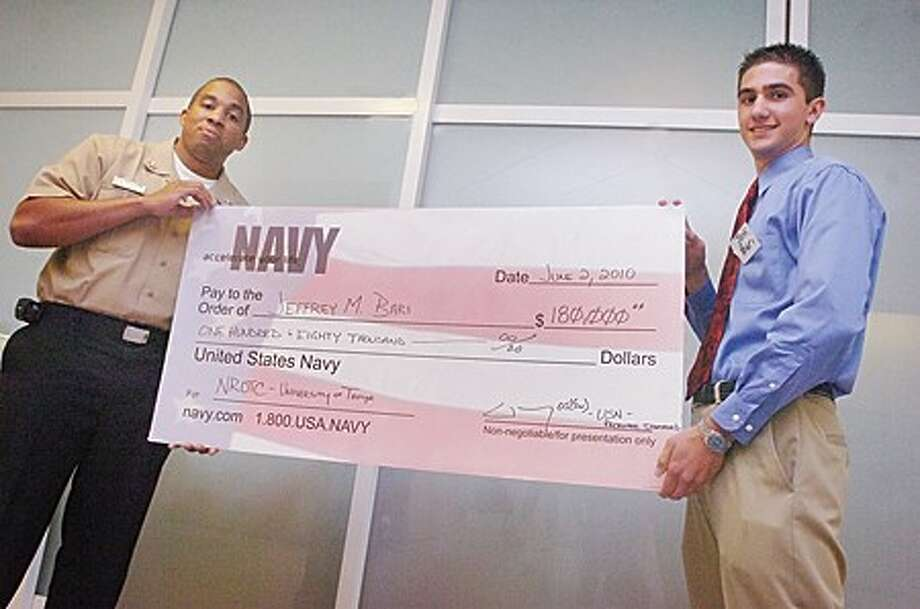 1st Class Petty Officer David Morey presents Brien McMahon student Jeffrey Bari a one hundred eighty thousand dollar scholarship from the U.S. Navy on Wednesday at the school''s Senior Scholorship Ceremony. hour photo/matthew vinci