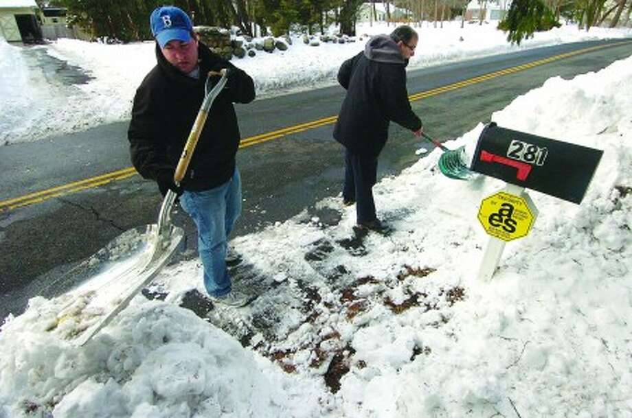 Photo/Alex von Kleydorff. Son Marshall and Dad Richard Weiss clear the snow from around their mail box on Silvermine Ave in Norwalk Wednesday.