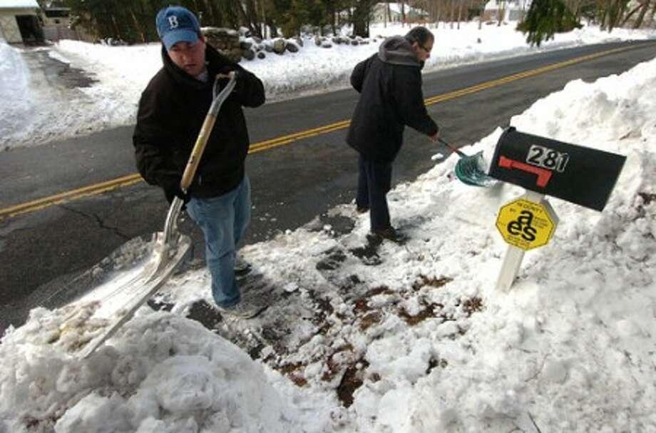 Photo/Alex von Kleydorff. Son Marshall and Dad Richard Weiss clear the snow from around their mail box on Silvermine Ave in Norwalk Wednesday.