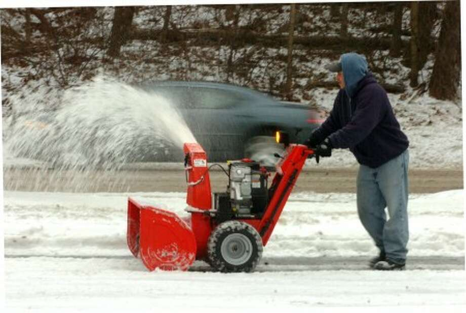 As traffic passes on a snowy Route 7 during a past snowstorm, Jorge Maisonet uses a snowblower to clear the area around the yard at Rings End lumber in Wilton. File photo by Alex von Kleydorff.