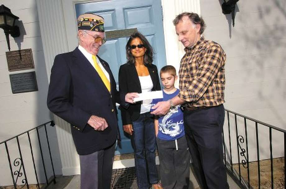 Wilton Villager Photo/Alex von Kleydorff. In this 2008 photo, from left, American legion Post 86 Commander Bing Ventres presents Shalini, Chris and Bill Madaras a check for the postage for shipping soccer balls to Iraq for the Kick for Nick program.
