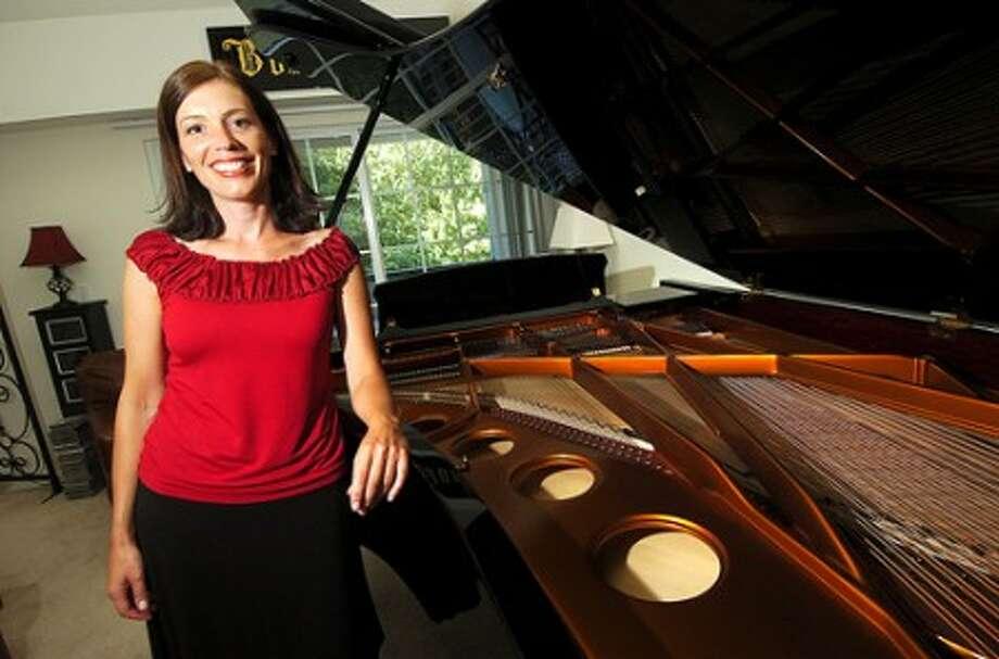 Photo/Alex von Kleydorff. Erica Faugner next to her piano in her Wilton home.