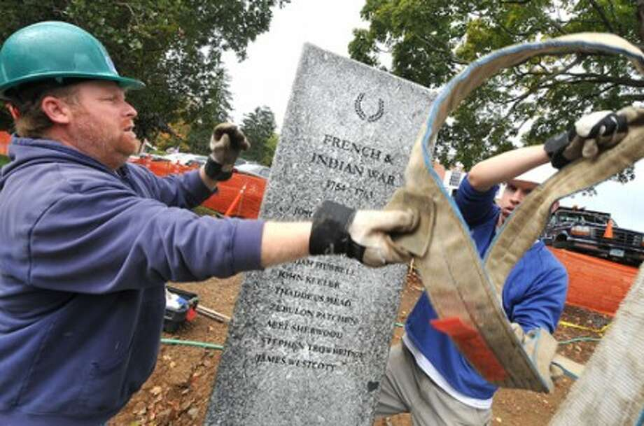 "Photo/Alex von Kleydorff. l-R Troy Gerow and Ben Rehmeyer with Freshwater Sone, move one of the stone column""s to its final spot at Wilton""s Veterans Memorial Green."