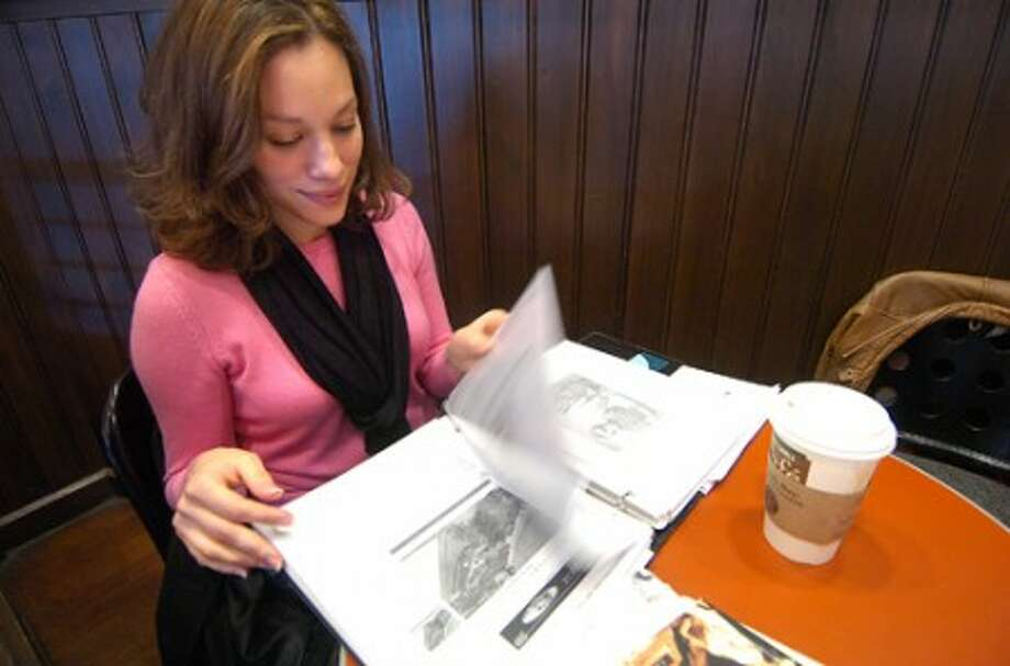 Photo/Alex von Kleydorff. At Barnes and Noble in Westport, Jessica Galan-Guzman leafs through one of the books of clips and vintage photographs she is working on for a project highlighting the Puerto Rican heritage in the state of Connecticut.
