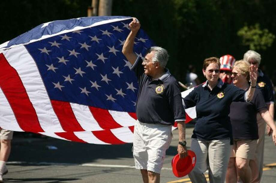 Ed Farris from the Norwalk Lion''s Club helps hold up a flag in Norwalk''s annual Memorial Day parade Monday morning. Hour Photo / Danielle Robinson