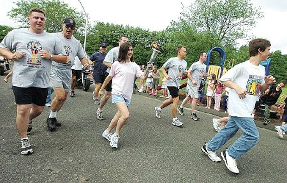 Special olympian jennifer Cassano carries the torch through the bus lane at Miller driscoll school alongside some of Wiltons police officers photo;alex von kleydorff file-06-16-06