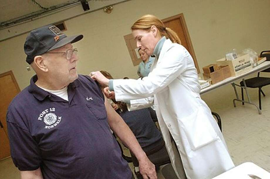 Roy Benedict receives his H1N1 vaccine Thursday at St. Phillip''s Church in Norwalk. Registered nurse Roxy Rosati was among the nurses distributing the vaccine/hour photo matthew vinci