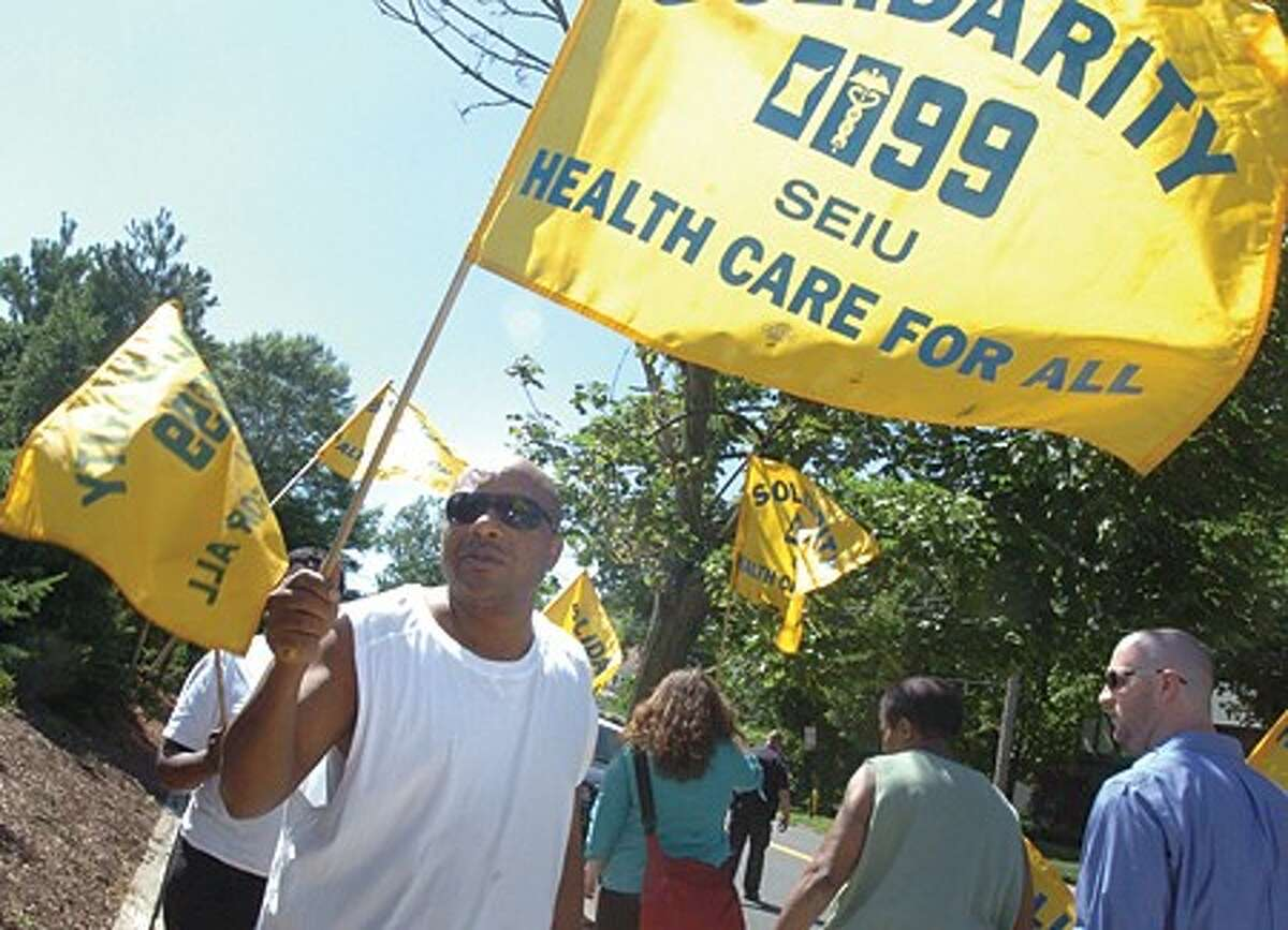 1199 member Larry Peltrop protests at the Tandet Center in Stamford. Care givers protested Wednesday about bouncing paychecks and cancelled health insurance for employees. hour photo/matthew vinci