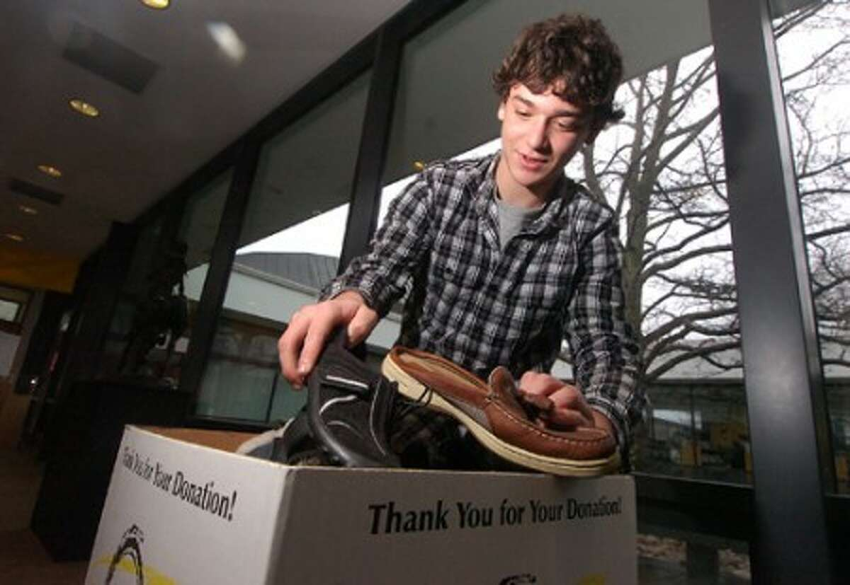 Photo/Alex von Kleydorff. Brett Bassock fills his donation bin at the Wilton Library with more dontaed shoes.