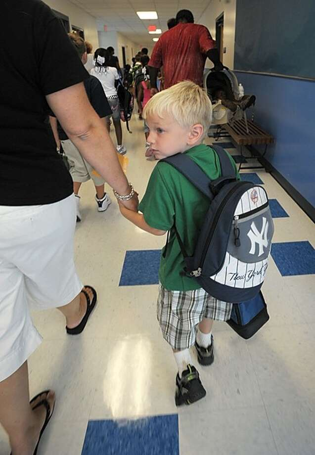 New Kendall Elementary School kindergartner Andrew Ehlers, 4, is lead to his new classroom on the first day of school Wednesday. Hour photo / Erik Trautmann