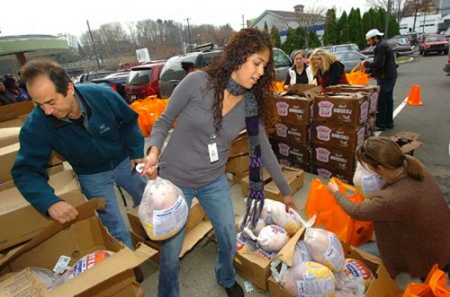 Photo/Alex von Kleydorff. Maritza Druin with The Norwalk Community Health Center with help from jesse Fink and Tricia Curry with the Fink family, sort turkeys into bags for some 200 needy families.
