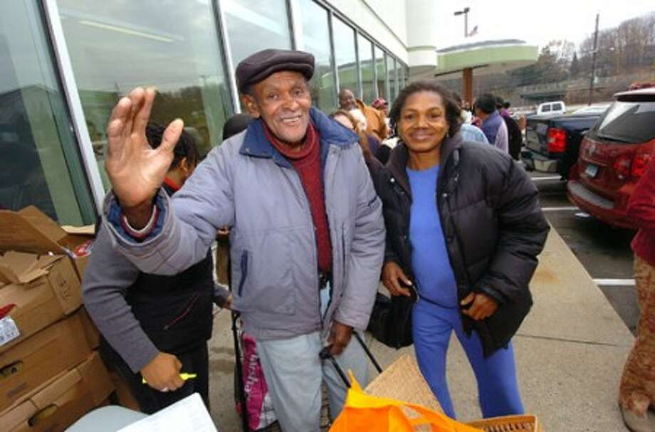 Photo/Alex von Kleydorff. julius Turnage and Ruby Martin give thanks to all who helped them at The Norwalk Community Health Center with their donated Thanksgiving dinner bag.
