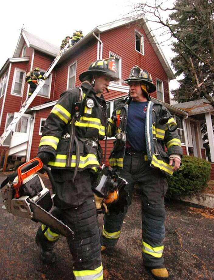 Photo/Alex von Kleydorff. Norwalk''s Engine 2 Firefighter David Janofsky talks with Truck 1''s Kevin Gilchrist Sr. after venting the roof of a multi family house that caught fire on Quintard St friday morning.