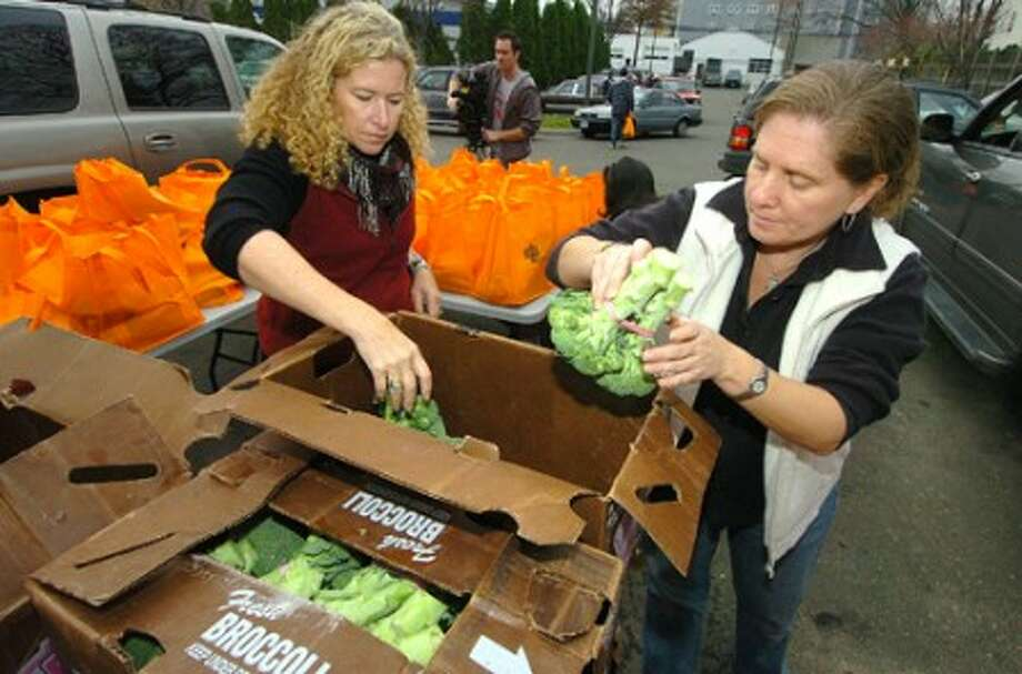 Photo/Alex von Kleydorff. Betsy Fink and Joan Briggs place broccoli into bags with all the Thanksgiving trimmings for The Norwalk Community Health Center to distribute to needy familys.