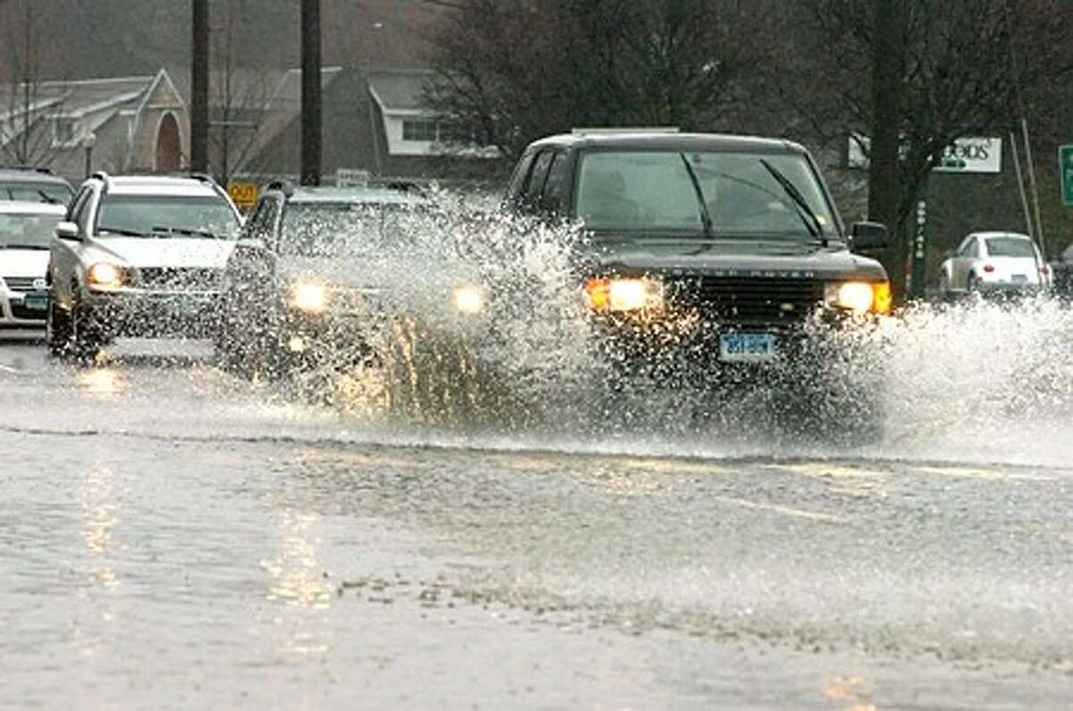 Heavy flooding slows traffic at the Westport/Norwalk line on Westport Avenue on Tuesday. hour photo/matthew vinci