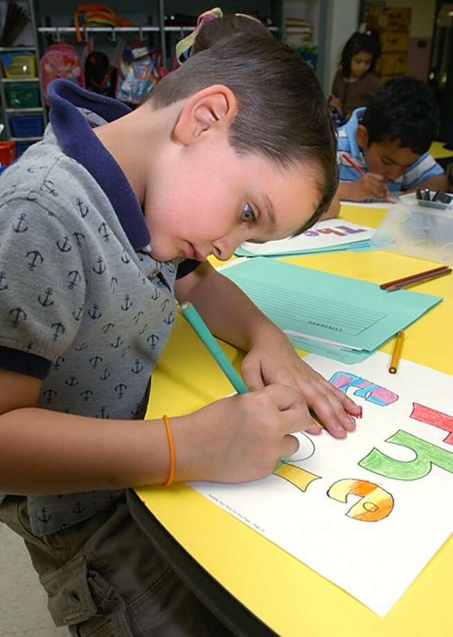 Naramake Elementary School kindergartner Jackson MacDonald illustrates a print for books he and each of his classmates will have published by the end of the school year, making them published authors. Hour photo / Erik Trautmann