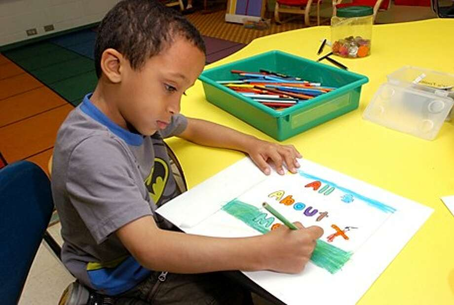 Naramake Elementary School kindergartner Hector Sarmiento illustrates a print for books he and each of his classmates will have published by the end of the school year, making them published authors. Hour photo / Erik Trautmann