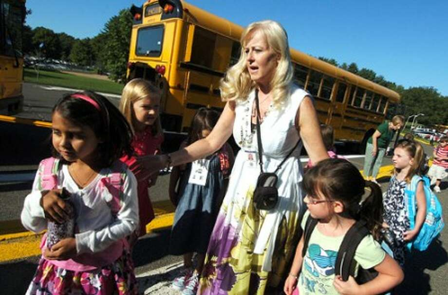 Photo/Alex von Kleydorff. Principal Cheryl jensen Gerner, helps first day students off the bus and into class at Miller Driscoll school.