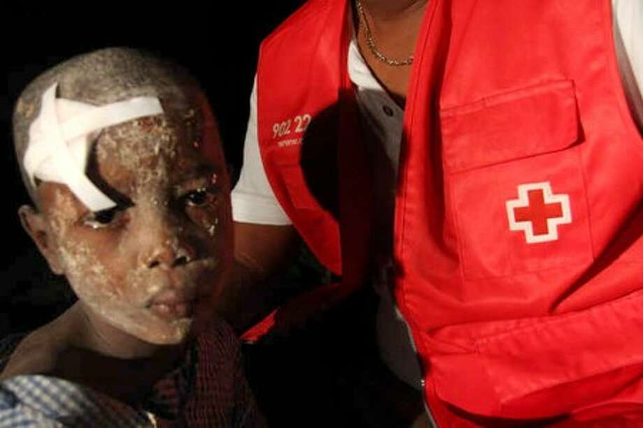 In this image made available by the American Red Cross in London, Wednesday Jan. 13, 2010, a young earthquake survivor is given first aid in a shanty town on the outskirts of Port au Prince, following a major earthquake in Haiti, Tuesday Jan. 12, 2010. Haitians piled bodies along the devastated streets of their capital Wednesday after the strongest earthquake to hit the poor Caribbean nation in more than 200 years crushed thousands of structures, from schools and shacks to the National Palace and the U.N. peacekeeping headquarters. Untold numbers were still trapped.(AP Photo/Matt Marek/American Red Cross, ho)