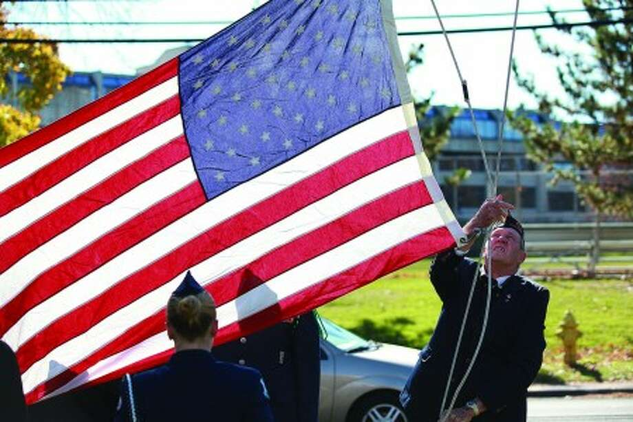 A flag is raised in honor of Jules Wallerstein who was remembered during the American Legion''s Veteran of the Month ceremony Sunday morning. Hour Photo / Danielle Robinson