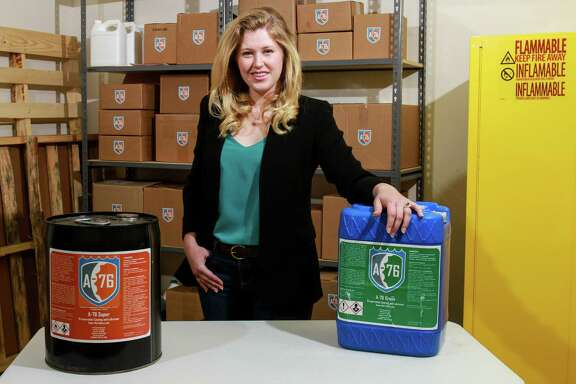 Lauren Thompson Miller, CEO and co-founder of A-76 Technologies, in the company's warehouse with 5-gallon cans of A-76 Super, on the left, and A-76 Green. The products also come in 55-gallon drums, and in aerosol or twist top bottles for household use. (For the Chronicle/Gary Fountain, May 20, 2016)