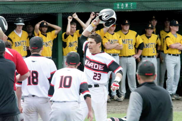 Warde's Giacomo Brancato is greeted at home plate after hitting a three-run home run in the sixth inning of the Class LL championship against Amity on June 11 at Palmer Field in Middletown. The Mustangs lost 4-3.