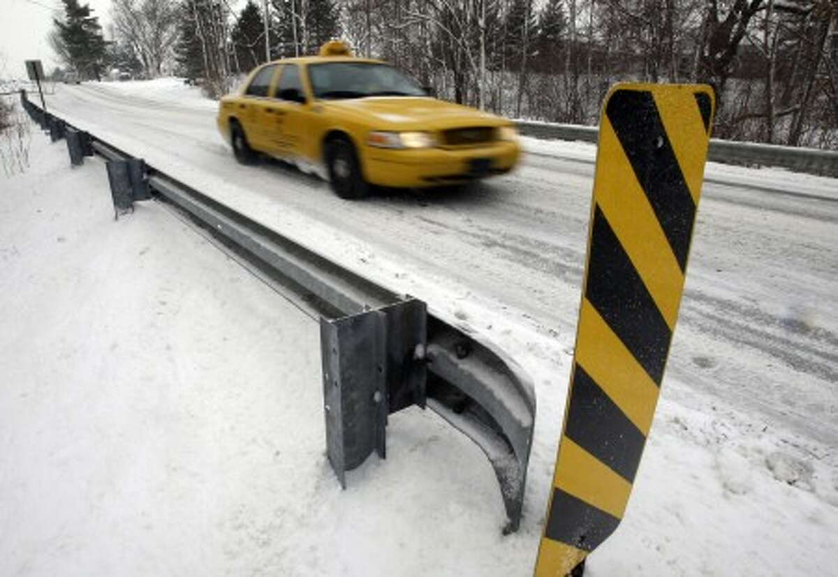 A taxi crosses a snow covered bridge in Carmel, Ind., Tuesday, Feb. 9, 2010. Snow accumulations of 5 to 7 inches (13-18 cms) are expected in Central Indiana. (AP Photo/Michael Conroy)