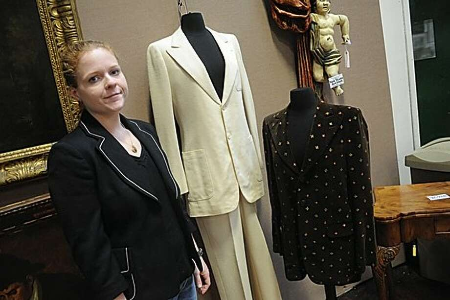 Auctioneer Kristi Braswell- Pantrese with two outfits worn by John Lennon will be at auction at the Braswell Galleries in Norwalk. On the left is the suit worn on the The Beatles album Abbey Road. On the right is a blazer he wore in his video for the song Imagine. hour photo/matthew vinci