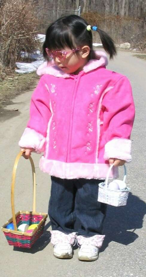 A child hunts for eggs at last year''s Hecksher Farm annual egg hunt. (contributed photo)