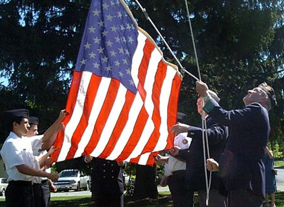 Post 12 sergeant at arms Bob Forbis raises the flag for the month of September for the Veteran of the Month John MacDonaldat the American Legion Post 12 ceremony on Sunday. hour photo/matthew vinci