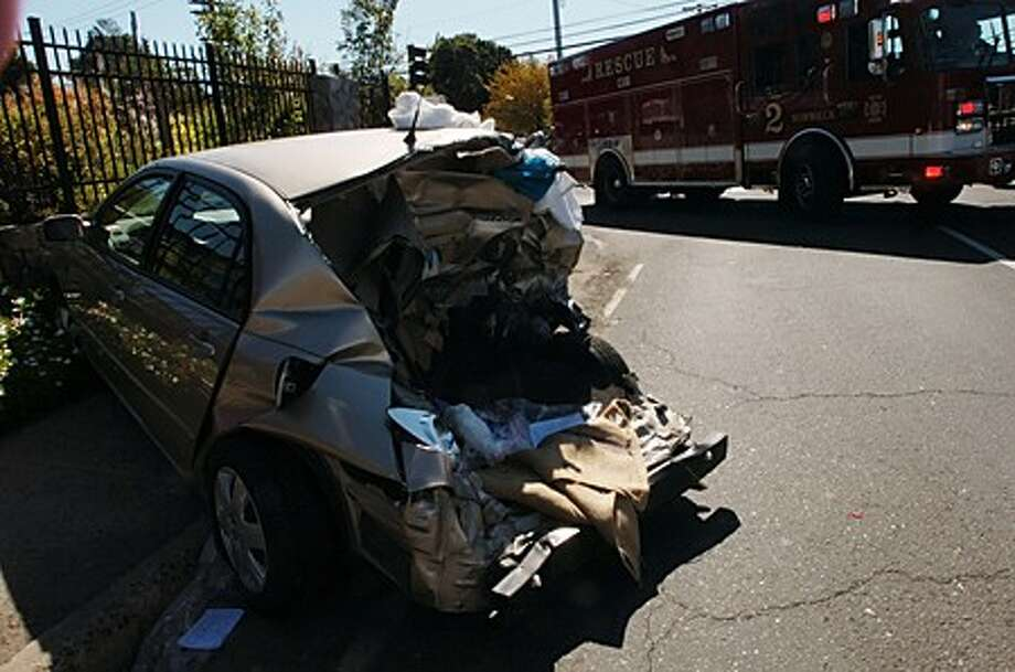 The rear end of a Toyota mangled in a multi-car accident where a Comfort King van collided with several vehicles Tuesday. Hour photo / Erik Trautmann