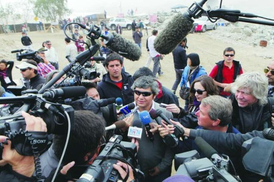 Rescued miner Juan Carlos Aguilar, center, is surrounded by the media prior to attending a mass at the San Jose mine near Copiapo, Chile Sunday, Oct. 17, 2010. Rescued miners gathered for a mass at the mine after being rescued on Wednesday. (AP Photo/Jorge Saenz)