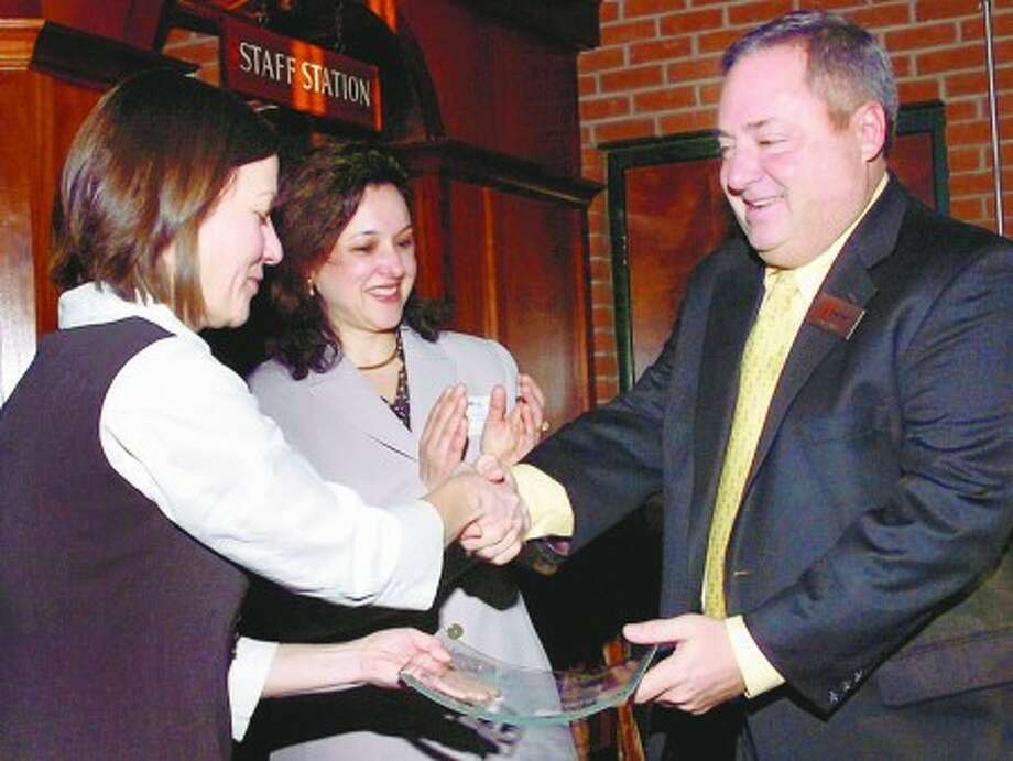 Aitoro Appliance co-owner Tony Aitoro recieves the Norwalk Education Foundation Small Business Partner in Education Award from Robin Guarieri, NEF event Co-Chair , While NEF Execuive Director Lauren Rosato looks on during the 8th Annual Business Partners for Education Awards Breakfast at the Brewhouse restaurant Wednesday morning. Hour photo / Erik Trautmann
