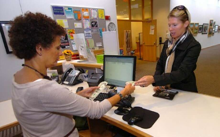 Photo/Alex von Kleydorff. Circulation Assistant Nevine Michaels collects some late fees from Jennifer Hulse at the Circulation desk at the Wilton Library