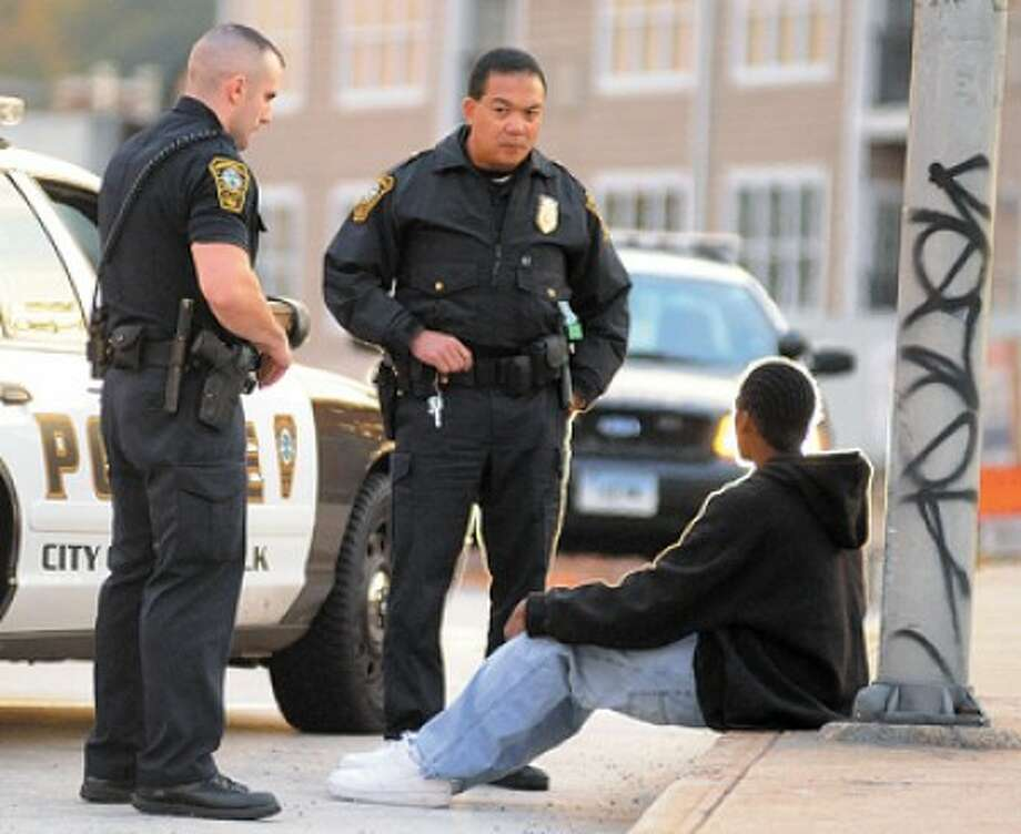 Hour Photo/JOHN NASH - Norwalk police have a talk with somebody they detained near the temporary Norwalk Bus Station after a shooting around the corner.