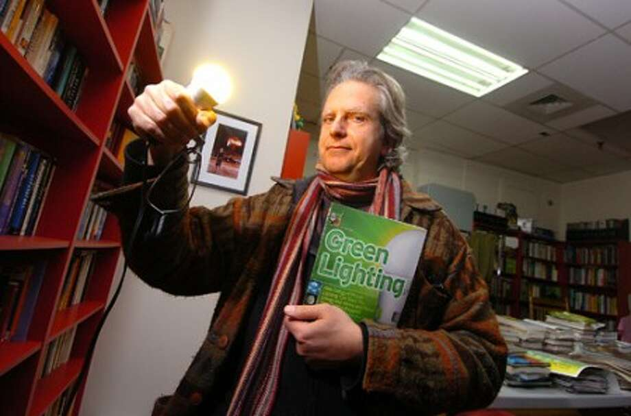 Photo/Alex von kleydorff. Remy Chevalier lights the way holding his Green lighting book, and an LED bulb while being illuminated by LED replacement tubes in a ceiling fixture at his green library, The Aquarium in Norwalk.