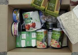 FILE - In this Jan. 8, 2014, shows the contents of a specially prepared box of food at a food bank distribution in Petaluma, Calif., part of a research project with Feeding America to try to improve the health of diabetics in food-insecure families. California plans to delay state-required warnings on metal cans lined with the chemical BPA, arguing too-specific warnings could scare stores and shoppers in poor neighborhoods away from some of the only fruits and vegetables available � canned ones, officials said Thursday, March 24, 2016. (AP Photo/Eric Risberg, File)