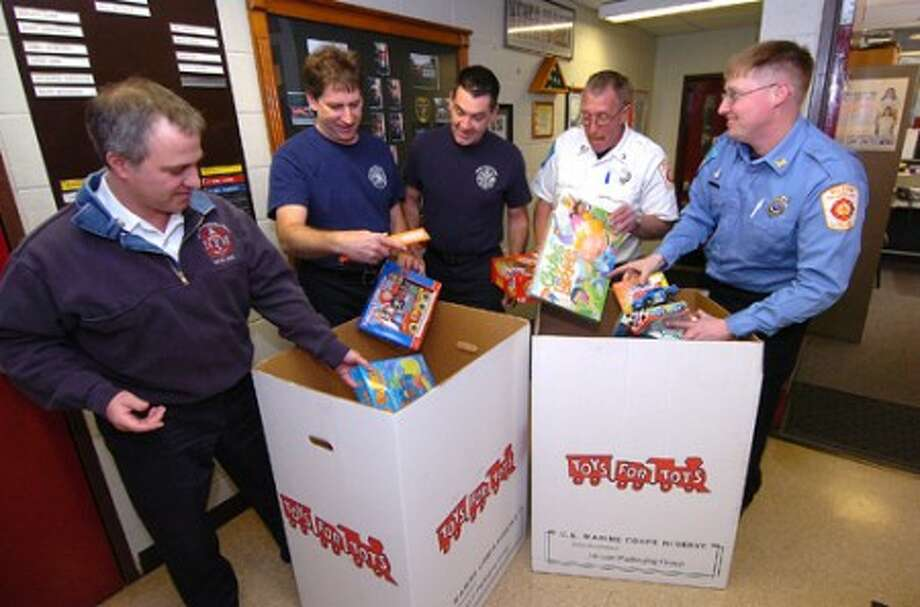 Photo/Alex von Kleydorff. Wilton Firefighters l-r Inspector Rocco Grosso, Brad Carlson, Kevin Plank, Capt. Stuart Carter and Coordinator Brian Elliott, place more toys in the Toys for Tots bin at Wilton Fire Headquaters.