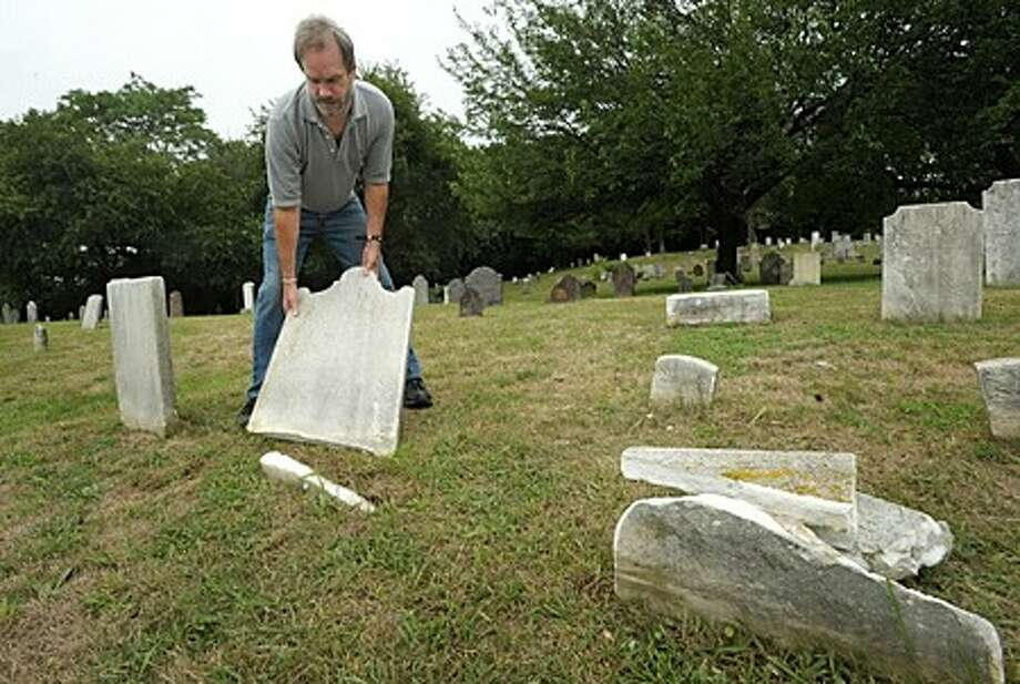Chairman of the Norwalk Historical Commission, David Park, investigates more damaged headstones at the historic Pine Island Cemetary Wednesday morning. Vandalisim had occured at the cemetary several years ago forcing the commission to install$10,000 of security lighting at the historic site. Hour photo / Erik Trautmann
